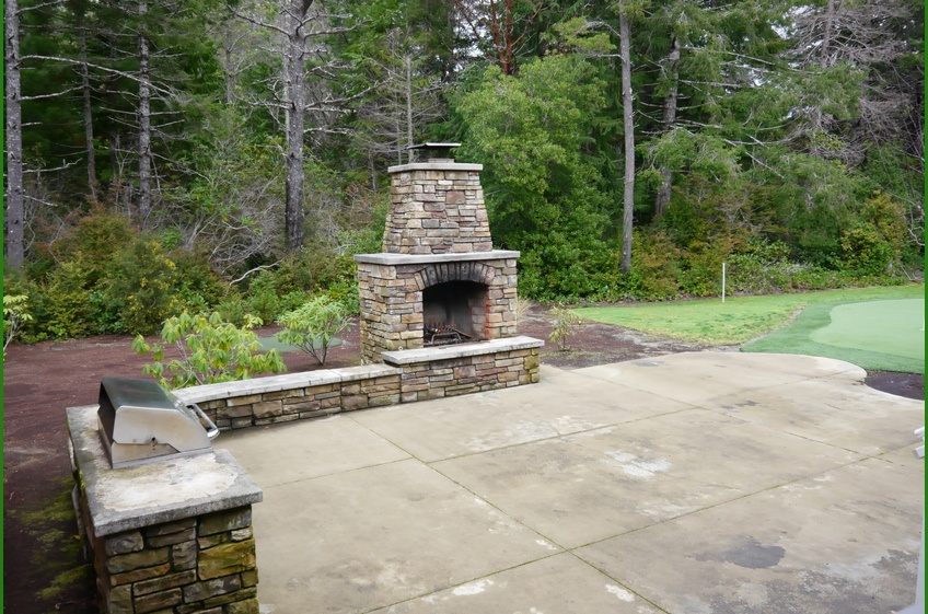 Back patio with stone fireplace, grill and putting green